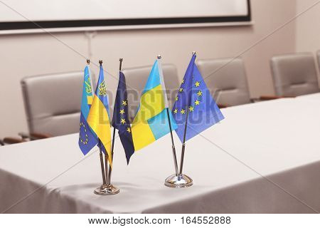 Small Flags Of The European Union And Ukraine On A White Table, A Conference Hall In The Background.