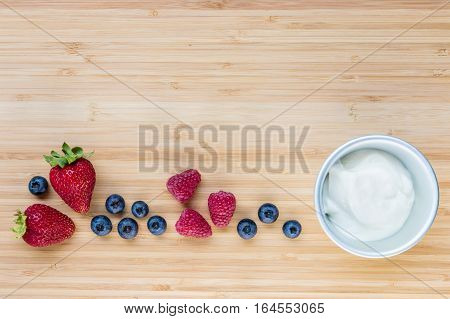 closeup of plain yoghurt in bowl with fresh berries on wooden board