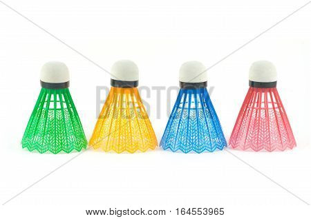 Four color synthetic badminton shuttlecocks in-line isolated on white background front view