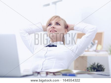 Business woman relaxing with her hands behind her head and sitting on a chair.