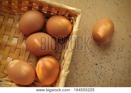 brown eggs in a basket on a textured surface with light and shade