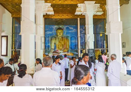 ANURADHAPURA SRI LANKA - NOVEMBER 26 2016: The large statue of Seated Buddha in the Image House of Bodhi Tree Temple full of pilgrims on November 26 in Anuradhapura.
