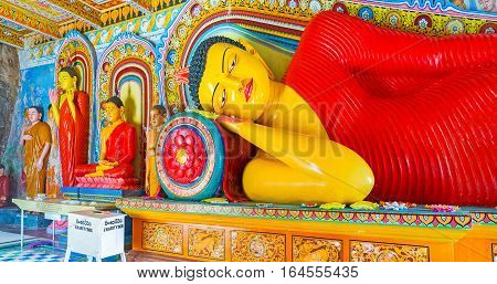 ANURADHAPURA SRI LANKA - NOVEMBER 26 2016: The Reclining Buddha in Isurumuniya Rock Temple with the smaller figures next to him on November 11 in Anuradhapura.