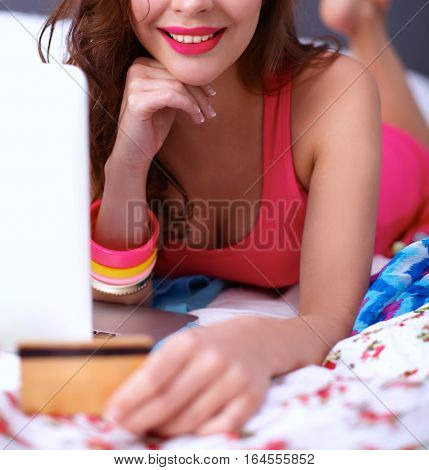 Beautiful woman lying on bed with a laptop and credit card.