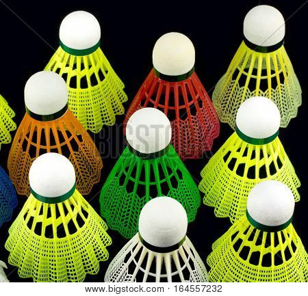 Many color badminton shuttlecocks with white corks on top isolated on black