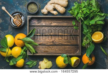 Ingredients for making natural hot drink with wooden tray in center. Oranges, mint, lemons, ginger, honeycomb, apple over plywood background, top view, copy space. Clean eating, detox, dieting concept.
