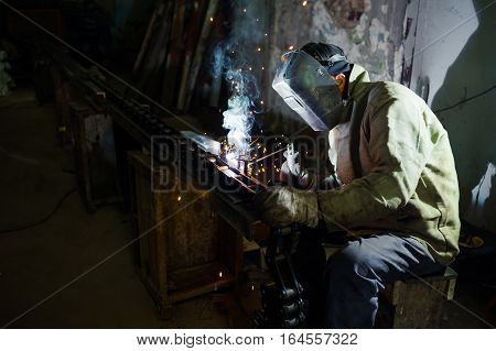 electric welding. electric welder welds metal parts factory