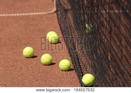 Ground court with yellow tennis balls before net closeup