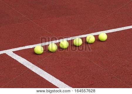 Line of six yellow tennis balls on red synthetic court side view
