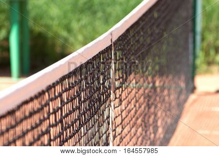 Top of tennis net on ground court outdoor side view closeup