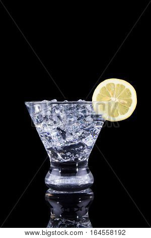 Sparkling Beverage In A Martini Glass With A Lemon Slice On A Black Background
