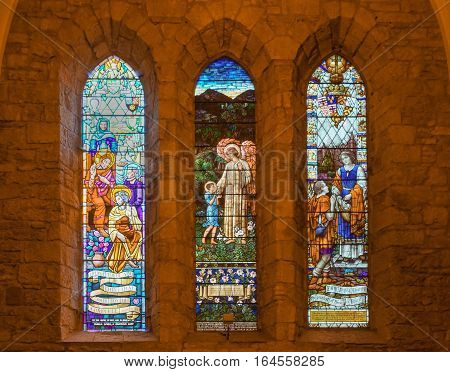 Dornoch Scotland - June 3 2012: Triple stained glass window on south transept of the cathedral of the Scottish Church. Shot inside church. Features charity faith hope and joy. Jesus Christ images in bright vibrant colors.