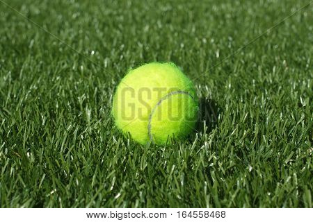 Yellow tennis ball lays on synthetic grass court field, closeup