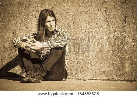 Man Long Haired Sitting Alone Sad On Grunge Wall