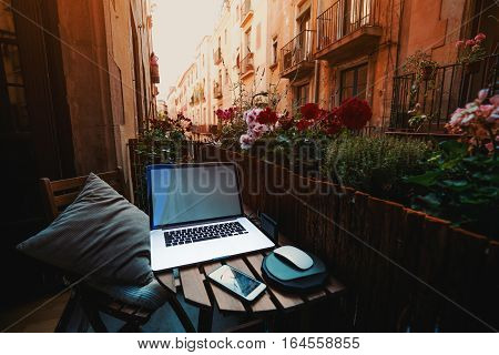 Cozy beautiful workspace on balcony with laptop smartphone wooden fence and a lot of flowers around on sunny summer day in historical district of Barcelona - El Born with facades of houses behind