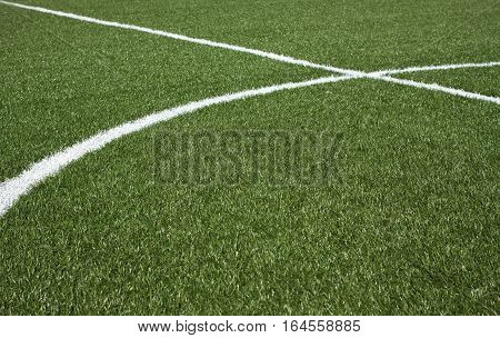 The center part of a soccer field with green synthetic grass and white lines on it horizontal view closeup