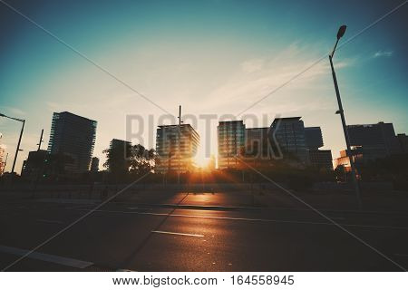 Wide angle shot of dramatic sunset with flare and godrays in residential district of Barcelona with houses in distance and part of highway in front with strong specular from the sun Spain