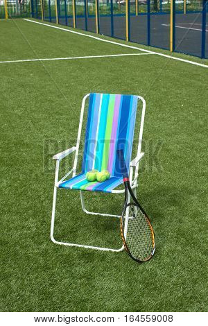 Metal armchair and tennis racket with four yellow balls on green synthetic grass court surface