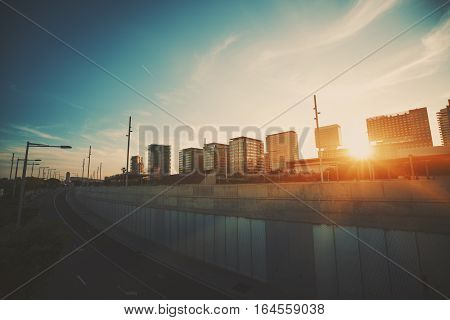 Wide angle shot of dramatic sunset with flare and godrays near highway in Barcelona with distant residential houses clear sky and spindrift clouds Forum district Spain