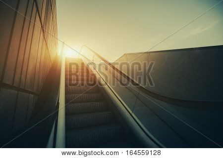 Outdoor city escalator stairway under evening sun with tiled wall on the left view from bottom vintage color filter