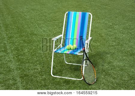 Metal armchair and tennis racket with four yellow balls on green synthetic grass court surface horizontal view