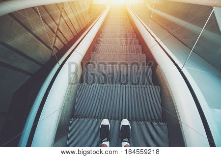 Outdoor city escalator stairway down feet of guy in gumshoes ready to go down; evening sun with tiled concrete wall on the left wide view from above vintage color filter