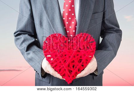 horizontal image of a torso of a man wearing a grey suit with a red valentine tie holding a red weaved heart with a sunset in the background.