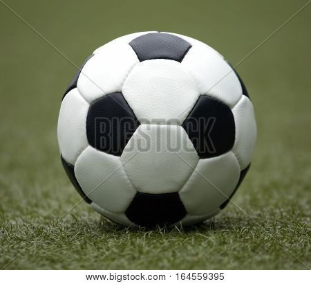 White and black ball for playing soccer  on synthetic grass  close-up