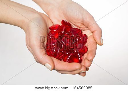 Close up of woman's hands holding red hearts on white background.