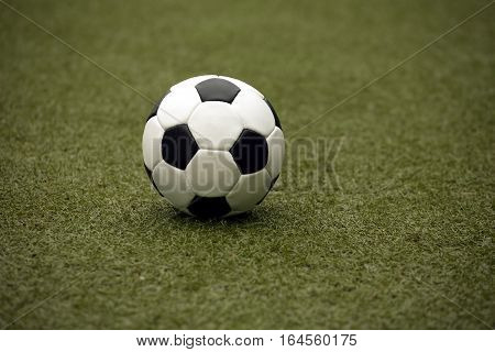 Classic white and black ball for playing soccer on synthetic grass  close-up