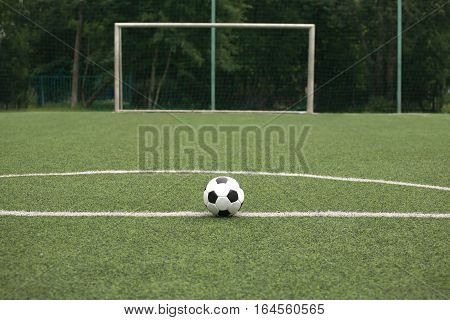 Classic white and black ball for playing soccer  on synthetic grass  playground against gate on sport field close-up
