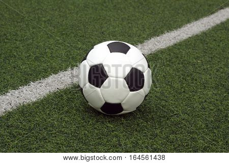 White and black ball for playing soccer  on synthetic grass side view close-up