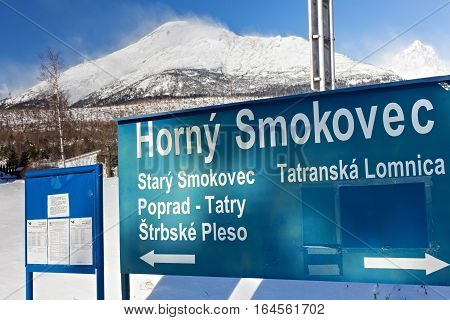 Blue road sign in the popular direction from Tatranska Lomnica to Stary Smokovec at the railway station of Horny Smokovec. In the High Tatras mountains region of Slovakia.