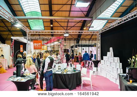 STRASBOURG FRANCE - JAN 8 2017: Couple visiting multiple booths and people at Salon du Marriage the guide exhibition for bridal and formal wear industry