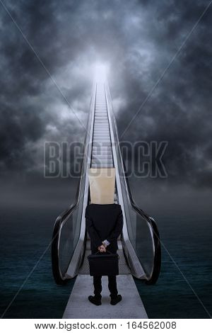 Anonymous businessman climbing stair to get the success door on the sky