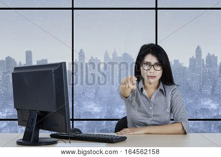 Picture of Asian businesswoman sitting in the office and pointing at you with computer on the table