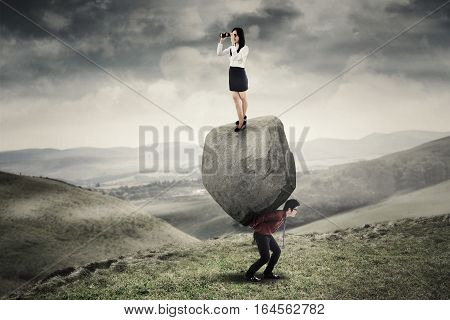 Businesswoman standing on a stone and looking through binoculars while her partner carrying the stone on the hill
