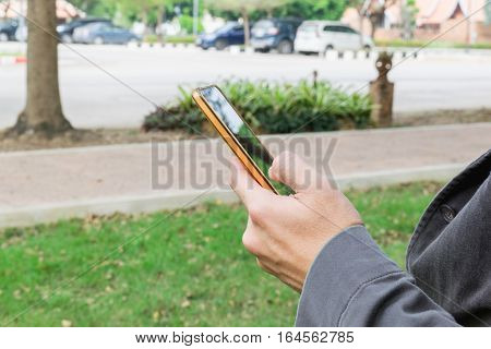 Human Using Smartphone In The Car Park. Wait Person For Travel Concept.