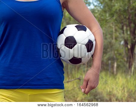 Teenage girl in blue shirt and yellow shorts holding classic ball for playing soccer. Closeup Photo