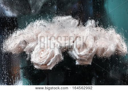 Bouquet of white roses behind window with rain drops background