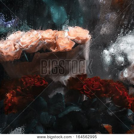 Bouquets of red white and yellow roses behind window with rain drops background