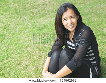 Beautiful Asian Woman Wearing Black Suit Is Smiling On The Green Grass. Positive Expression Woman Co