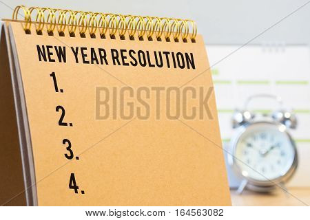 Resolution on a notepad with blurred background alarm clock and calendar