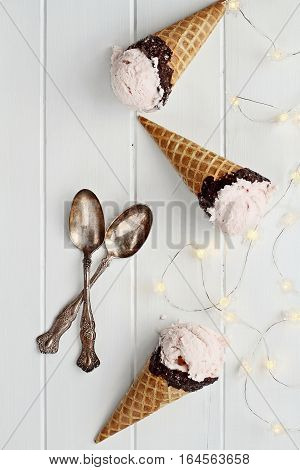 Top view of pink strawberry ice cream in waffle cones shot over a rustic wooden background with fairy lights and antique spoons.