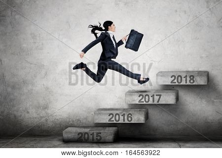 Picture of female entrepreneur running on the stairs with number 2017 toward 2018 while carrying a briefcase