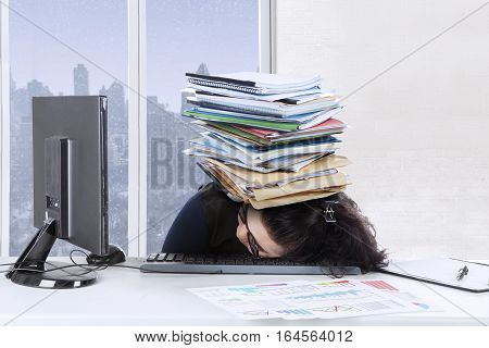 Frustrated woman sleeping on the keyboard with stack of documents over her head winter background on the window