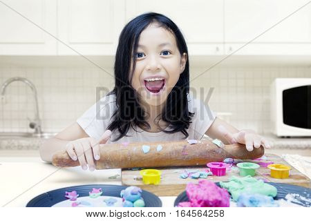 Portrait of little girl holding rolling dough while making handicraft with playdough