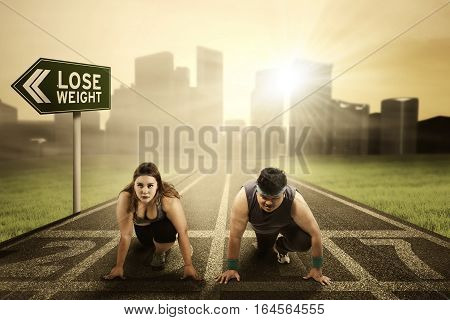 Portrait of overweight people ready to compete and try to chase their dream with numbers 2017 on the running track and text of losing weight on the signboard