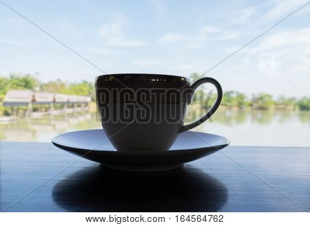 Silhouette Of A Cup Of Coffee And Breathtaking Views Of The Fishing Park From Coffee Cafe.