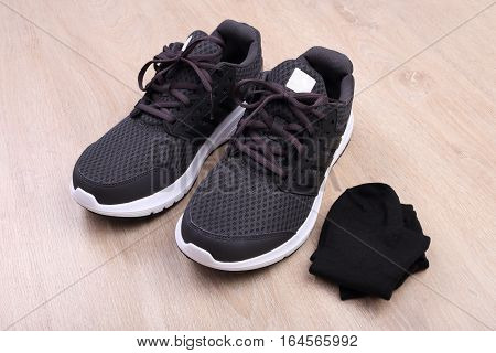 Black sport shoes with sock on wooden background